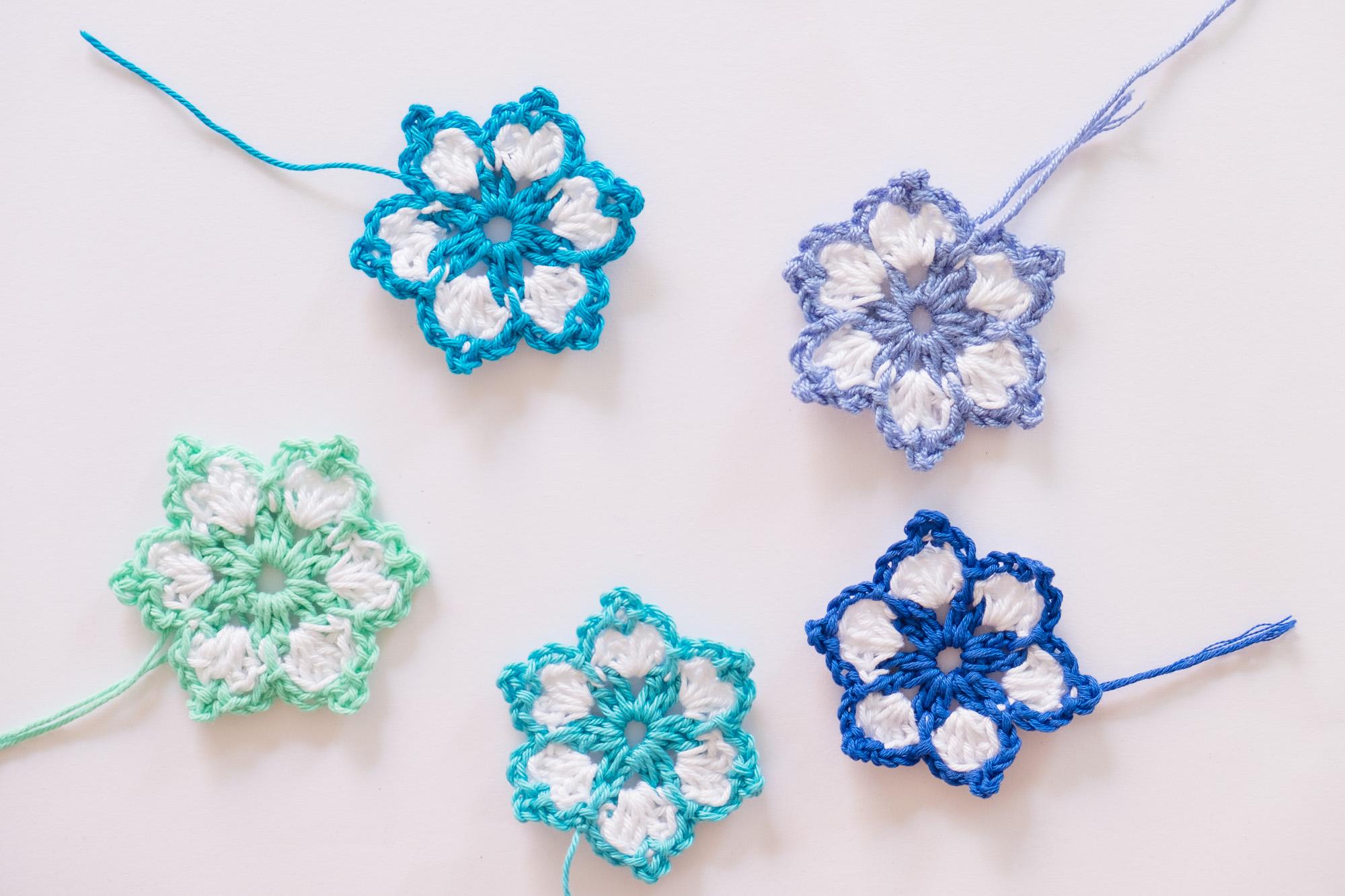 Flores de ganchillo en diferentes tonos de azul .